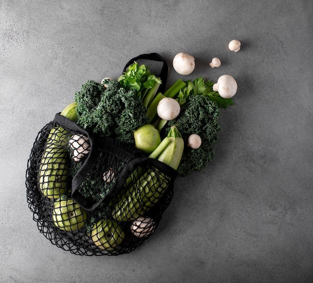 Groene groenten en fruit in een eco-tas op een grijze tafel