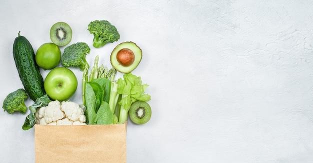 Groene groenten en fruit in een papieren zak op een lichtgrijze achtergrond
