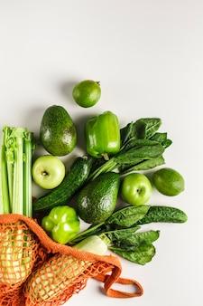 Groene groenten en fruit in oranje touwzak