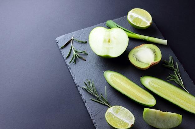 Groene groenten en fruit op donkere leisteen bord. concept natuurlijke groene producten. avocado, kiwi, limoen en appel. rozemarijn, dille en bieslook op stenen bord