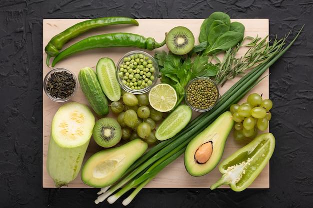 Groene groenten en fruit op snijplank
