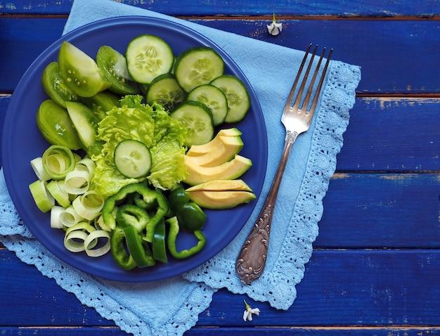 Groene groenten en fruit - sla, komkommer, prei, avocado, appel en groene paprika op blauwe houten ondergrond