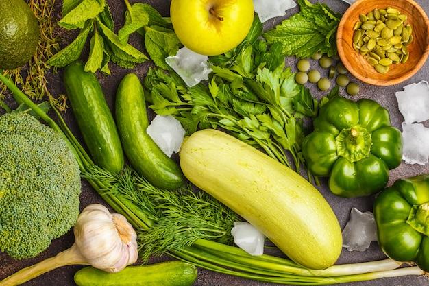 Groene groenten op een donkere ondergrond. plantaardige veganistische dieetvoeding: courgette, paprika, broccoli, komkommers, avocado, appel, kruiden. gezond levensstijlconcept.