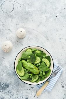 Groene groentesalade met spinazie, avocado, groene erwten en olijfolie in kom op lichtgrijze leisteen