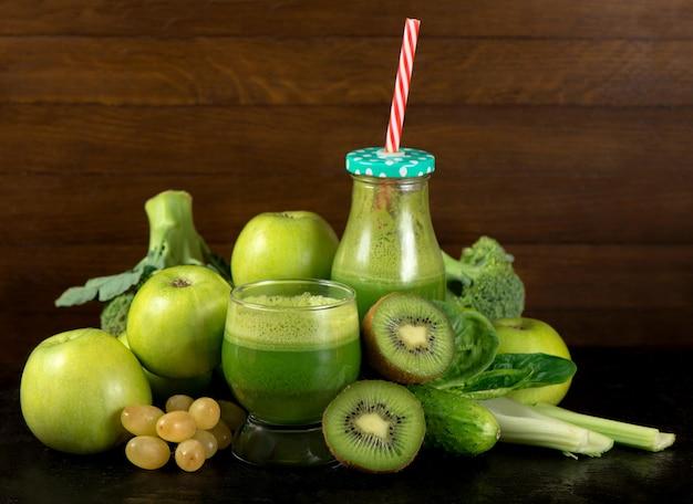 Groene groentesmoothie in potten en ingrediënten op de witte houten muur. dieetconcept met tekstruimte. detox. vegetarisch eten