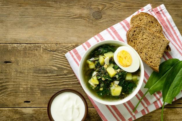 Groene groentesoep met zuringbladeren en eieren in een witte kom