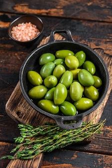 Groene grote olijven in kom met tijm