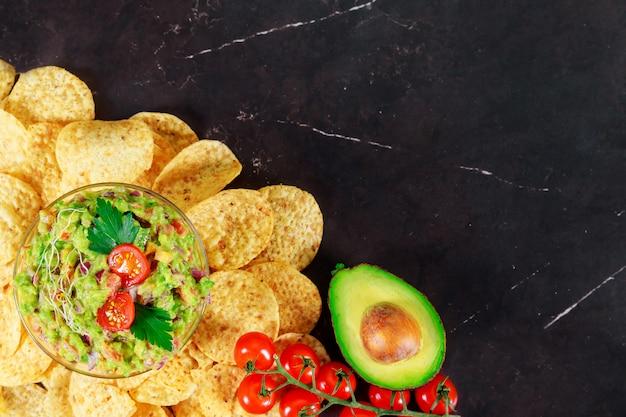 Groene guacamole met nachos en avocado op steenachtergrond