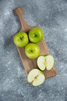 Groene hele en gesneden appels op een houten bord.