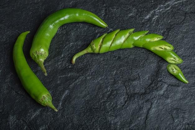 Groene hete chili peper gesneden of geheel op zwarte achtergrond. hoge kwaliteit foto