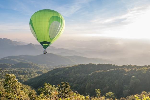 Groene hete luchtballon over hoog berglandschap bij zonsondergang