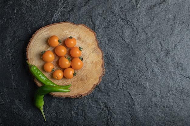 Groene hete peper en kersentomaten op het houten stuk met zwarte achtergrond. hoge kwaliteit foto