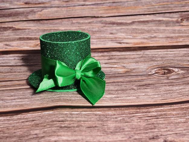 Groene hoed met gouden munten en klaver op houten tafel, st patricks dag concept.