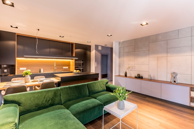 Groene hoekbank in de buurt van witte tafel met bloemen in gezellig appartement interieur met grijze keuken