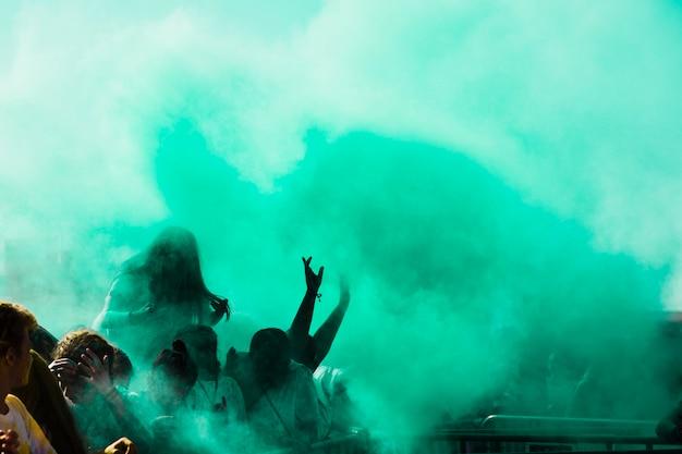 Groene holi-kleurpoeder over de menigte