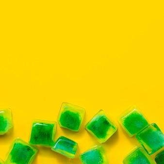 Groene ijsblokjes op gele achtergrond