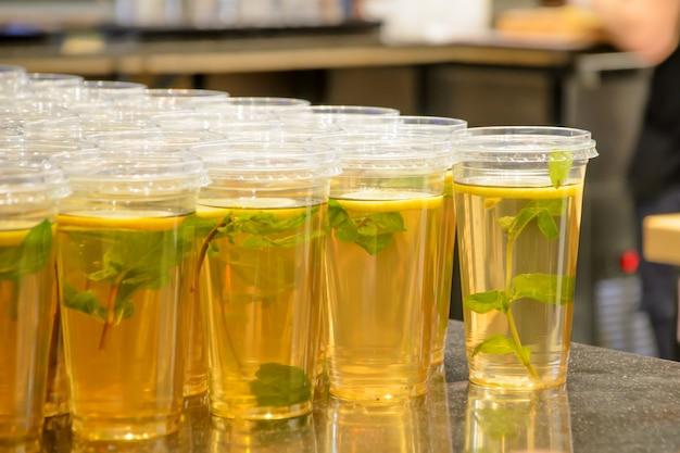 Groene ijsthee met munt en citroen in plastic transparante glazen met een deksel op cafételler