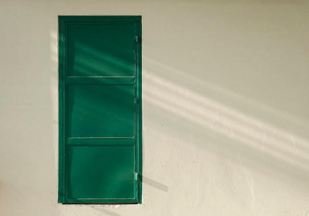 Groene ijzeren deur met betonnen muur en kopie ruimte.