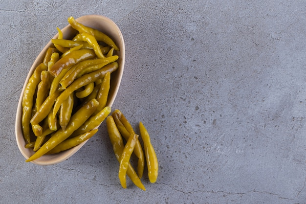 Groene ingelegde chili peper geplaatst op een stenen oppervlak.