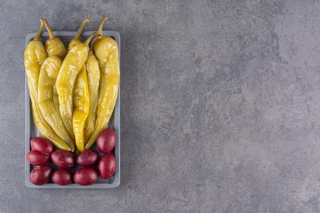 Groene ingelegde chili peper geplaatst op stenen tafel.