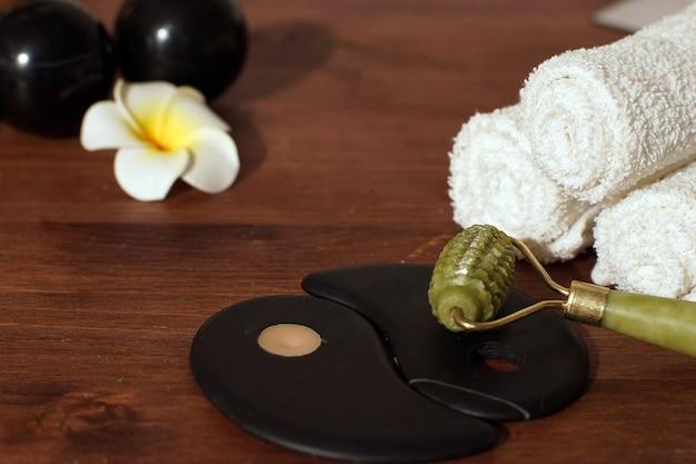 Groene jade roller voor gezichtsmassage op tafel met spa-rekwisieten en yin yang-teken