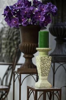 Groene kaars op een kandelaar op de marmeren achtergrond van bloemen en vazen