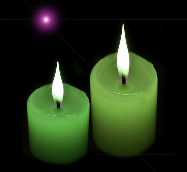 Groene kaarsen op zwart.