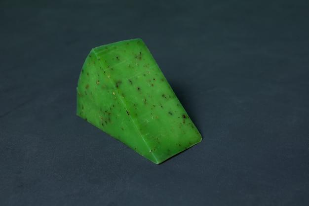Groene kaas met basilicum, close-up. driehoekstuk van gastronomische pestokaas op donkere achtergrond