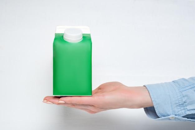 Groene kartonnen doos of verpakking van tetra-pack met een dop in een vrouwelijke hand.