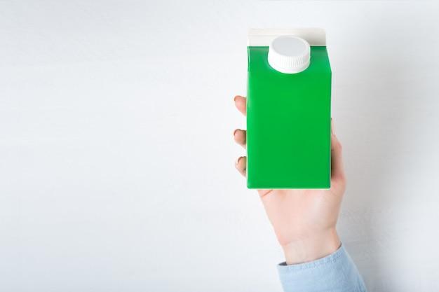 Groene kartonnen doos of verpakking van tetrapak met een dop in een vrouwelijke hand. witte achtergrond