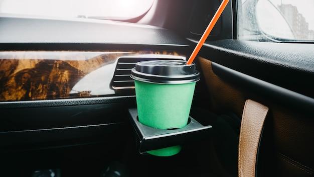 Groene kartonnen kop koffie in de auto in de handen drankje op de reis