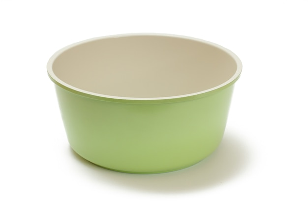 Groene keramische kokende keukenpan op witte geïsoleerde achtergrond.