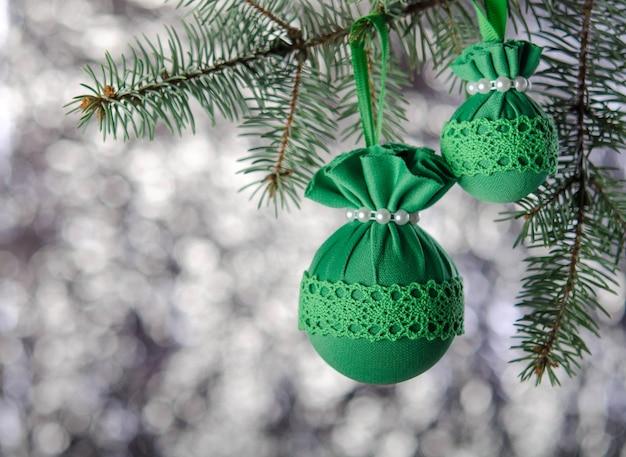 Groene kerstballen met een patroon op een pluizige vuren tak