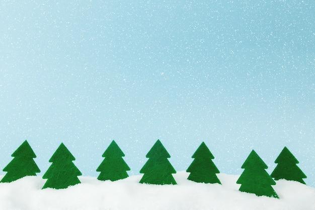 Groene kerstbomen op blauw met nepsneeuw.