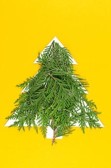 Groene kerstboom gemaakt van naaldboomtakken op pastel geel oppervlak
