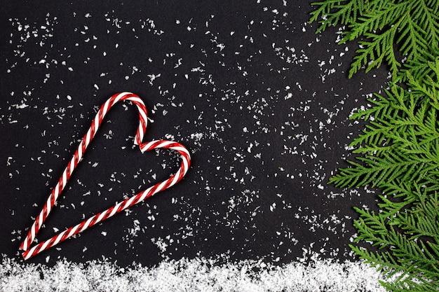 Groene kerstboom gemaakt van naaldhout takken en sneeuwvlokken op een donker