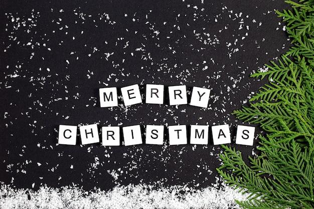 Groene kerstboom gemaakt van naaldhout takken en sneeuwvlokken op een donkere achtergrond. minimale compositie achtergrond. nieuwjaar en kerstmis concept.