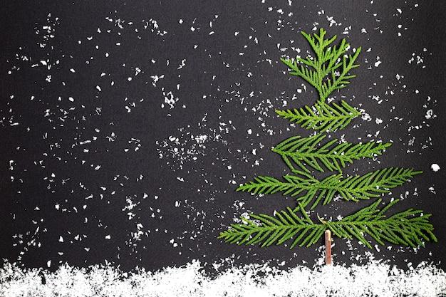 Groene kerstboom gemaakt van naaldhout takken op een donkere achtergrond. minimale compositie achtergrond. nieuwjaar en kerstmis concept.