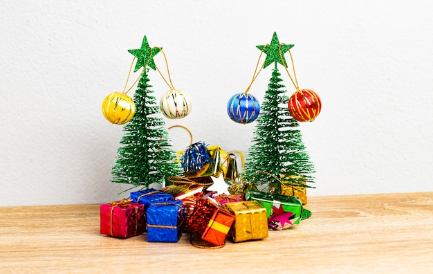 Groene kerstboom met kleurrijke geschenkdozen en kleine mooie bal op de houten tafel en witte achtergrond