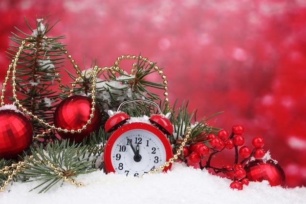 Groene kerstboom met speelgoed en klok in de sneeuw op rood
