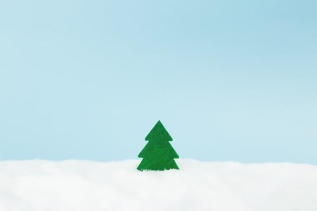 Groene kerstboom op blauw met nep sneeuw.