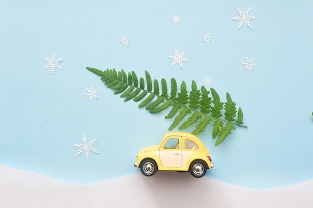 Groene kerstboom op gele speelgoedauto met sneeuwvlokken