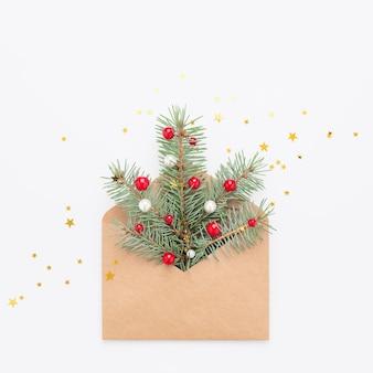 Groene kerstboom symbool in ambachtelijke papieren envelop, confetti op witte kopie ruimte achtergrond.