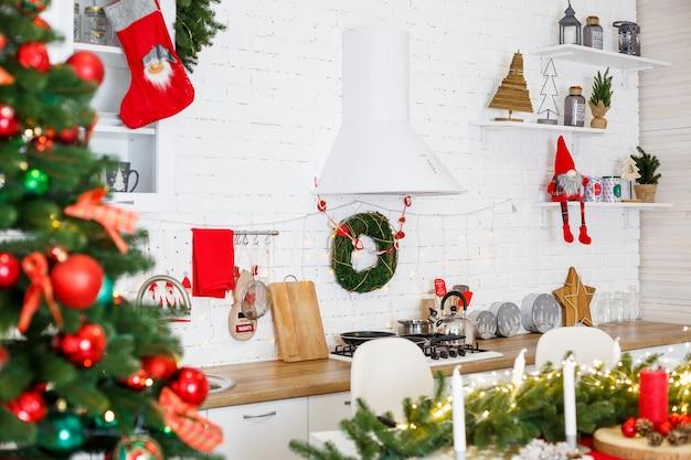 Groene kerstboom, versierd met ballen, kerstversieringen, gele slingers. nieuwjaarsversieringen in de keuken. nieuwjaar. decoraties in huis voor kerstmis.