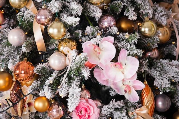 Groene kerstboom versierd met speelgoed, ballen en bloemen met bokeh-effect lichten