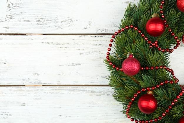 Groene kerstkrans met versieringen op houten achtergrond
