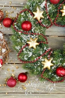 Groene kerstkrans met versieringen op houten vloer