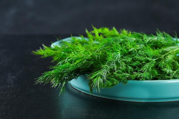 Groene keukenkruid dille op een zwarte achtergrond