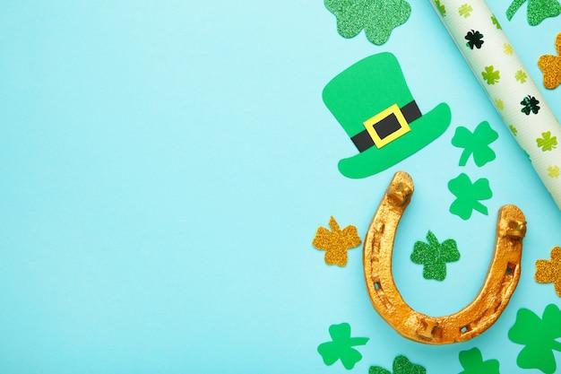 Groene klaverblaadjes en gouden hoef op blauwe achtergrond voor st. patrick's day holiday. bovenaanzicht.