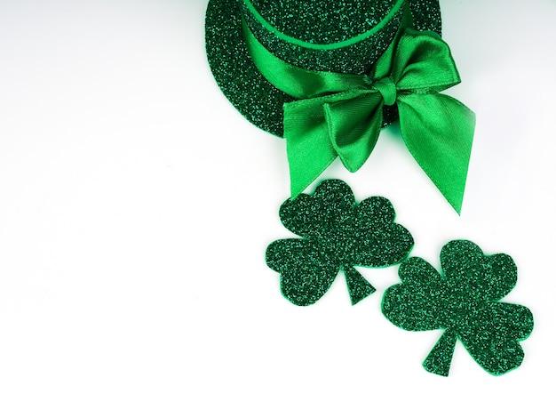 Groene klaverblaadjes of klavers, groene hoed geïsoleerd op een witte achtergrond. st. patrick's day vakantie concept. lente achtergrond.